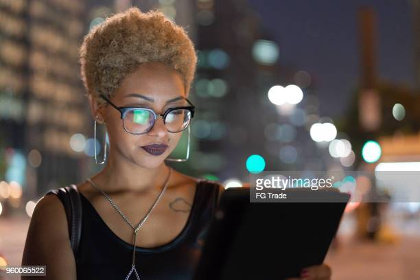 young woman using tablet at night - afro caribbean ethnicity stock pictures, royalty-free photos & images