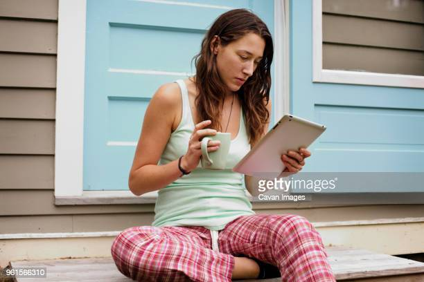 Young woman using tablet computer outside house while holding coffee mug