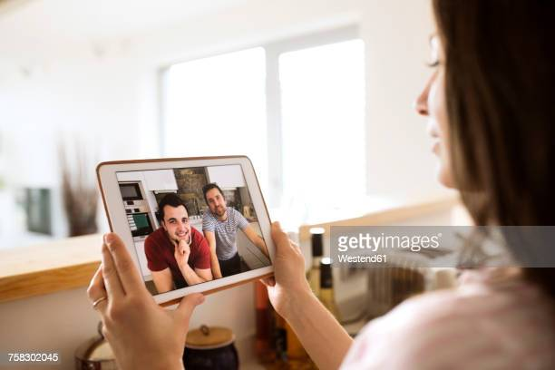 young woman using tablet for video chat at home - long distance relationship stock pictures, royalty-free photos & images