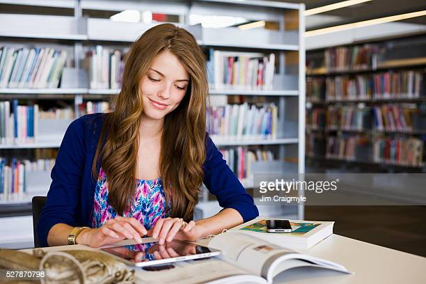 Young woman using tablet in library