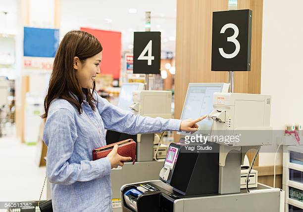 Young woman using the cash register of self-service