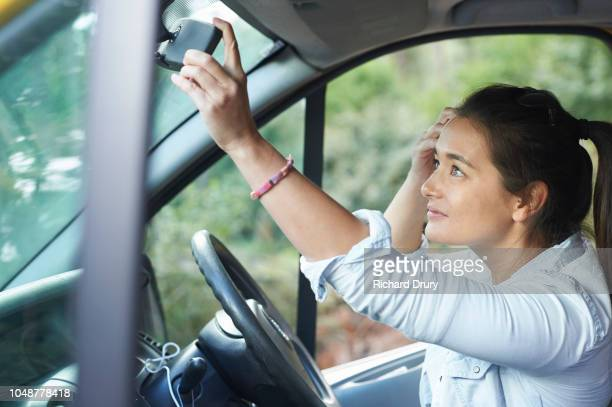 Young woman using the rear mirror of her van to adjust her hair