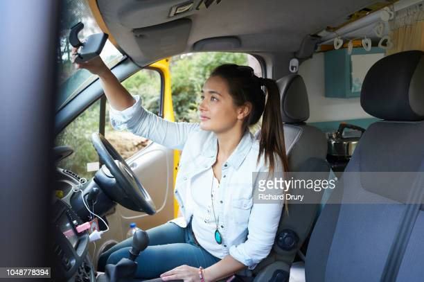 Young woman using the rear mirror of her van to check her look