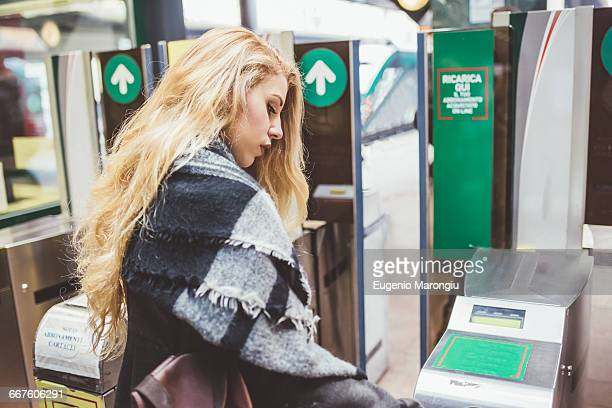 Young woman using ticket barrier in train station
