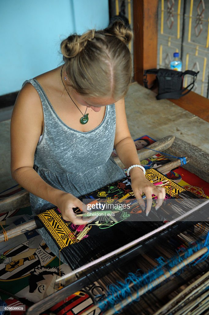 Young woman using traditional Lombok weaving loom : Stock Photo