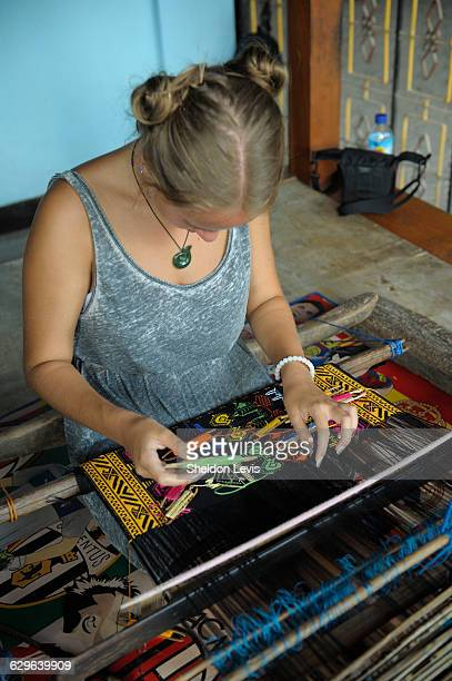 Young woman using traditional Lombok weaving loom