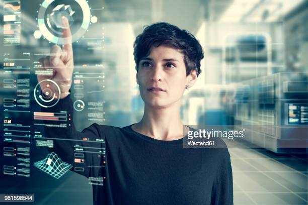 Young woman using transparent touchscreen display, Composing
