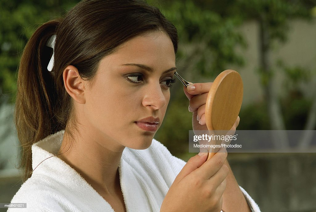 Young woman using tweezers to shape eyebrow, close-up : Stock Photo