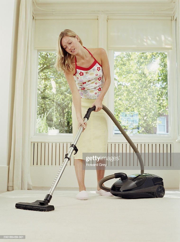 Young woman using vacuum cleaner : Stock Photo