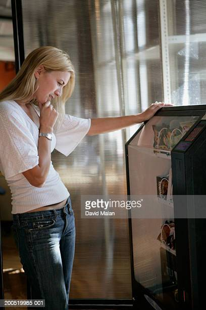 Young woman using vending machine, side view