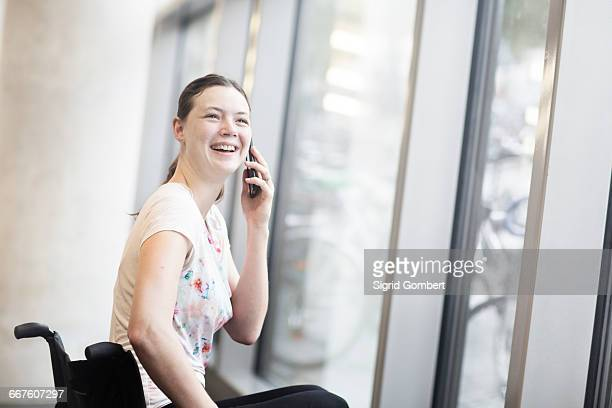 young woman using wheelchair at entrance door talking on smartphone - sigrid gombert stock pictures, royalty-free photos & images