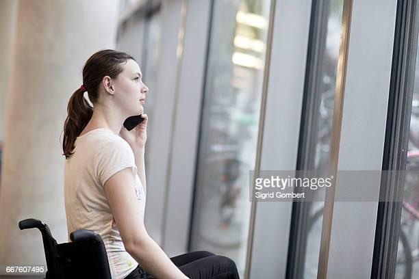 young woman using wheelchair gazing through entrance window talking on smartphone - sigrid gombert fotografías e imágenes de stock