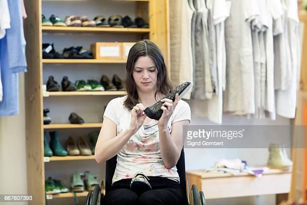 young woman using wheelchair looking at shoes in shop - sigrid gombert 個照片及圖片檔