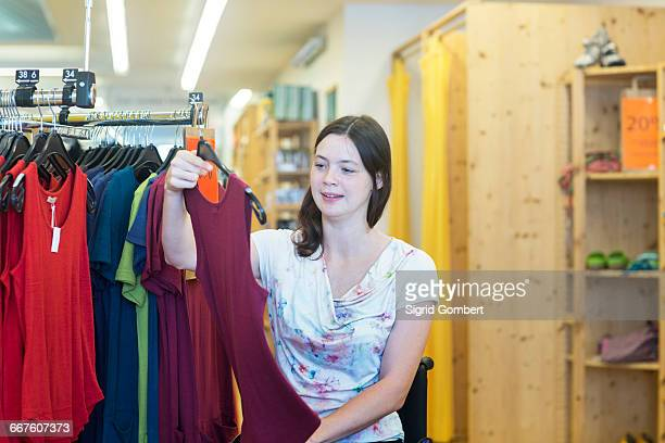 young woman using wheelchair looking at vest in shop - sigrid gombert 個照片及圖片檔