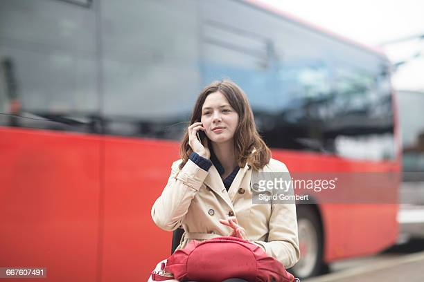 young woman using wheelchair talking on smartphone at city bus station - sigrid gombert stock pictures, royalty-free photos & images