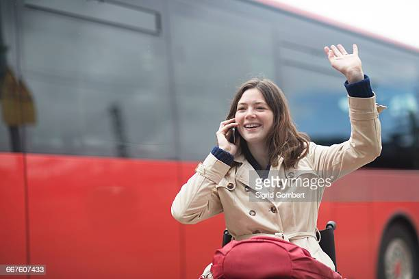 young woman using wheelchair waving from city bus station - sigrid gombert fotografías e imágenes de stock