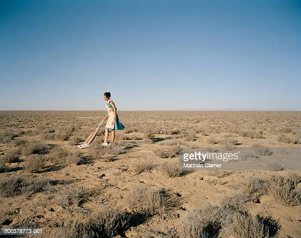 young woman vacuming in desert, side view - out of context stock pictures, royalty-free photos & images