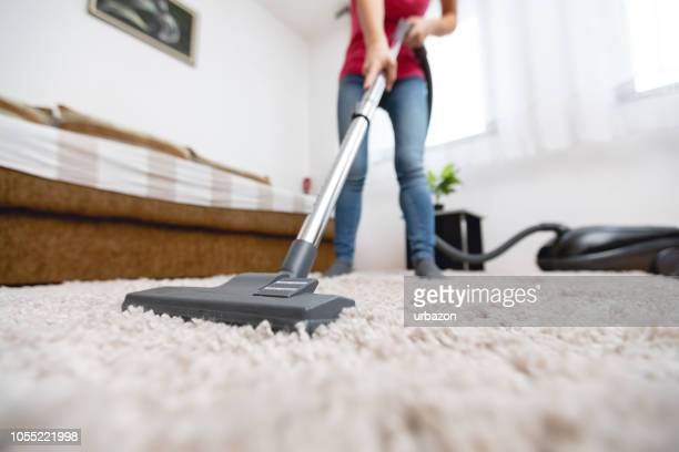 young woman vacuuming house - cleaner stock pictures, royalty-free photos & images