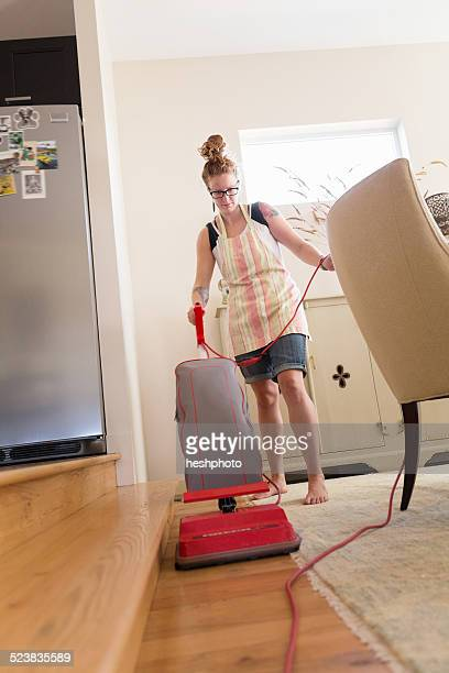 young woman vacuuming with green cleaning products - heshphoto stock pictures, royalty-free photos & images