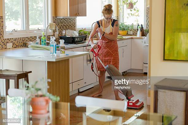 young woman vacuuming with green cleaning products - heshphoto stock-fotos und bilder