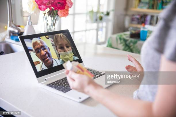 young woman video call with doctors - adamkaz stock pictures, royalty-free photos & images