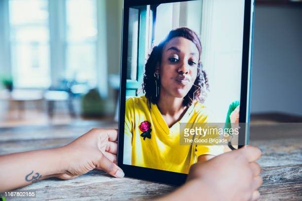 young woman video conferencing with friend on digital tablet - selbstportrait stock-fotos und bilder