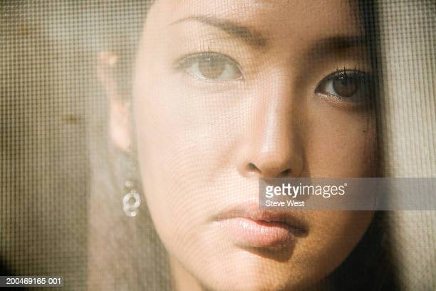Young woman, view through screen door, portrait