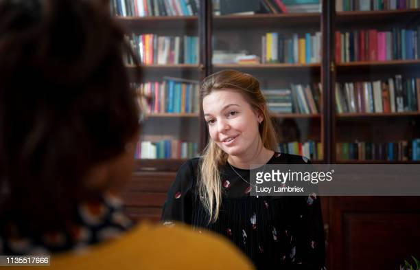 young woman visiting a counselor - lucy lambriex stockfoto's en -beelden
