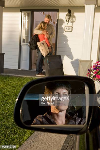 Young woman visiting dad with mom looking on