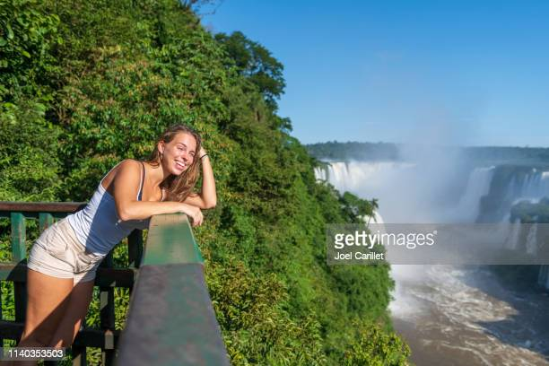 young woman visiting iguazu falls in brazil - iguacu falls stock pictures, royalty-free photos & images