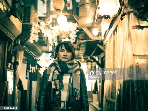 伝統的な日本の狭い路地を訪れる若い女性 - のれん ストックフォトと画像