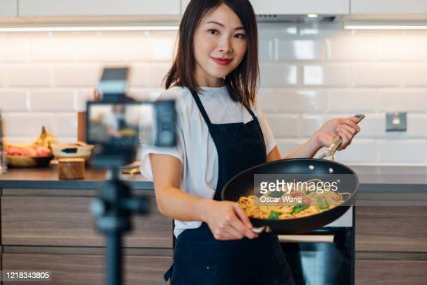 young woman vlogging cooking at home - 映像撮影 ストックフォトと画像