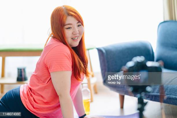 young woman vlogging her yoga routine - chubby asian woman stock pictures, royalty-free photos & images