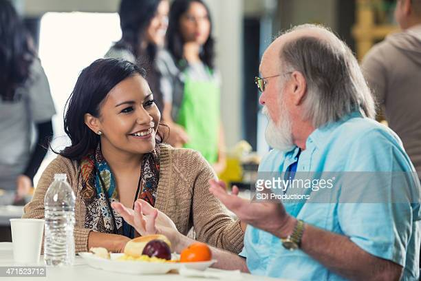young woman volunteering in food bank and talking to senior - depression bread line stock pictures, royalty-free photos & images