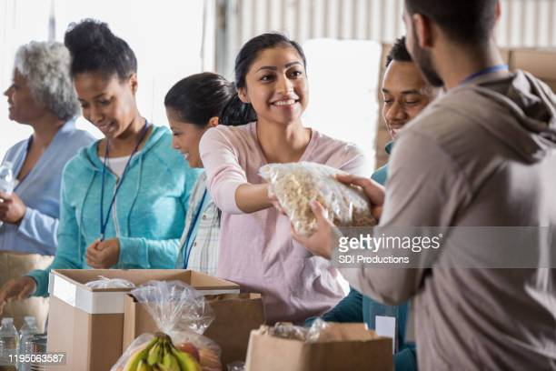young woman volunteering in food bank - volunteer stock pictures, royalty-free photos & images