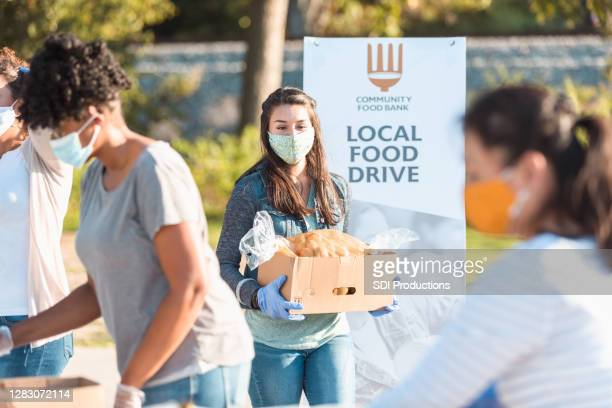 young woman volunteers at food drive during covid-19 - charity and relief work stock pictures, royalty-free photos & images