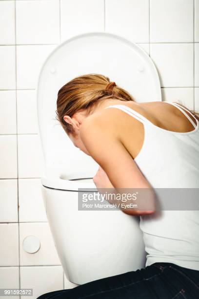 young woman vomiting in toilet bowl at bathroom - vomiting stock photos and pictures