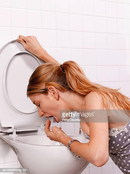 young woman vomiting into toilet bowl, close-up - bulimia fotografías e imágenes de stock