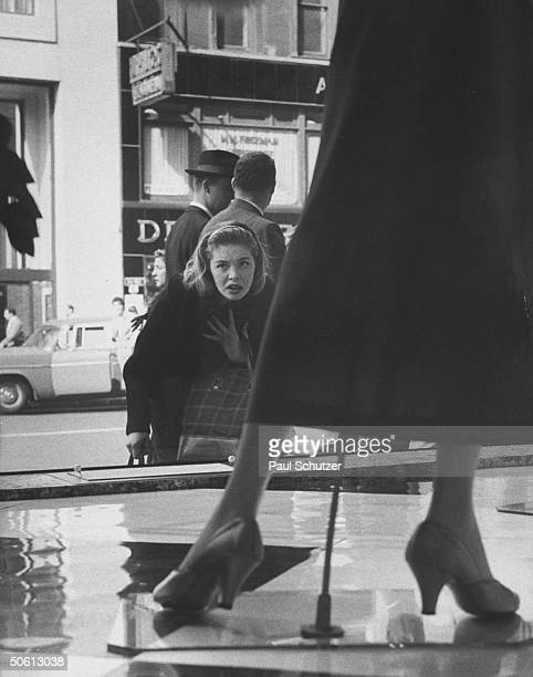 Young woman w dubious look on her face gazing into Bloomingdale's window where Diorinspired longer skirts are being displayed