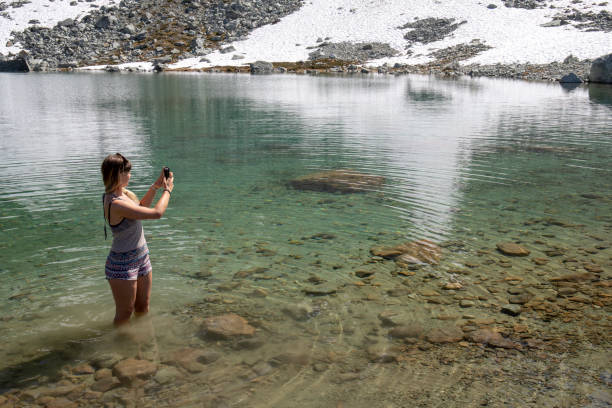 Young woman wades into a mountain lake and takes a photo