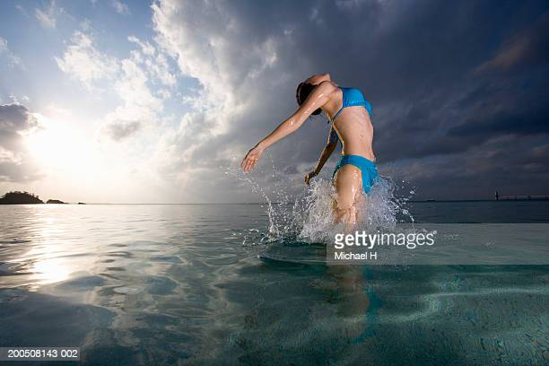 Young woman wading in sea, arms outstretched, head back, side view