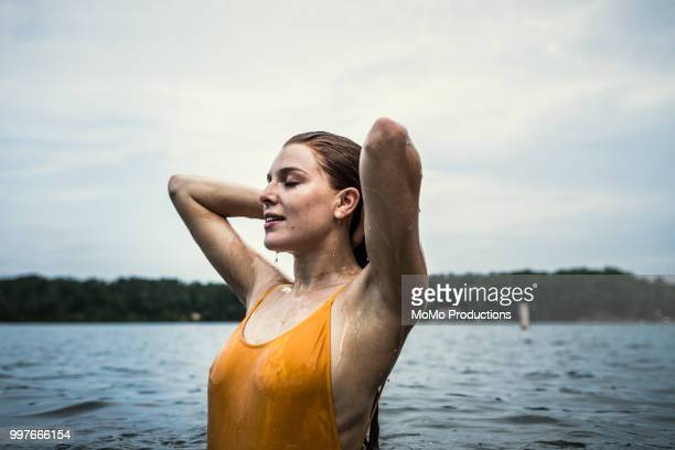 young woman wading in water at lake - waist deep in water stock pictures, royalty-free photos & images