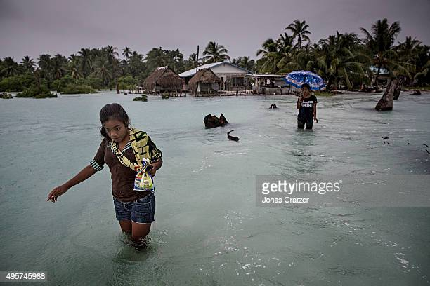 A young woman wading through the salty sea water that flooded the way home to her village Eita The people of Kiribati are under pressure to relocate...