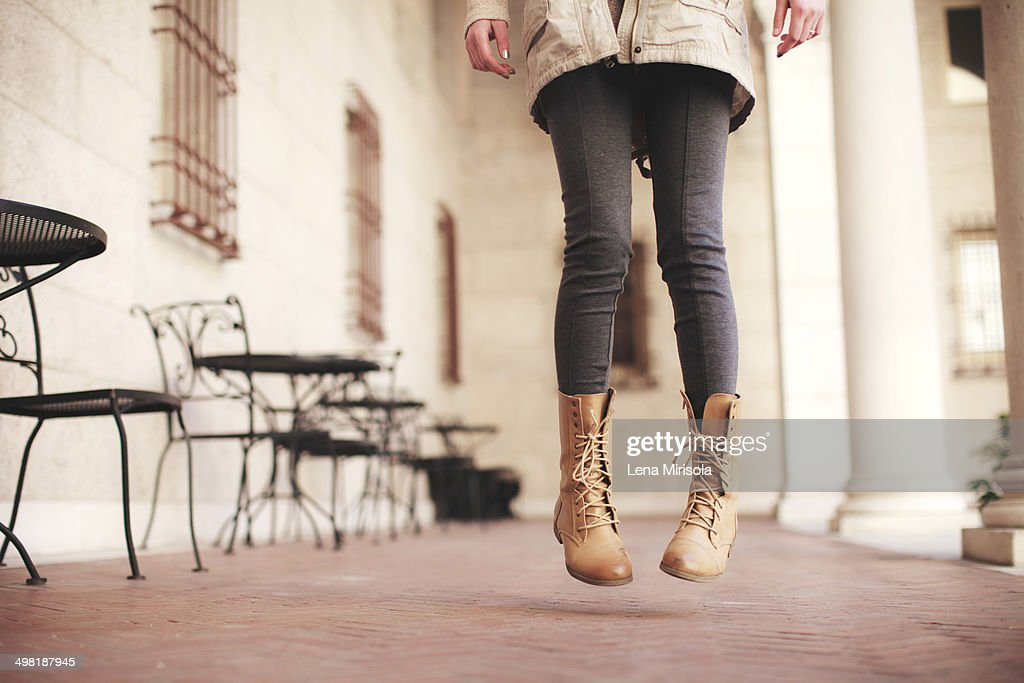 Young woman waist down jumping next to sidewalk cafe : ストックフォト