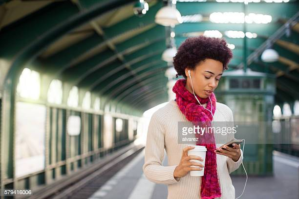 Young woman waiting at subway station using cellphone
