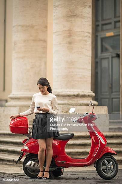 Young woman waiting by moped, Piazza del Popolo, Rome, Italy