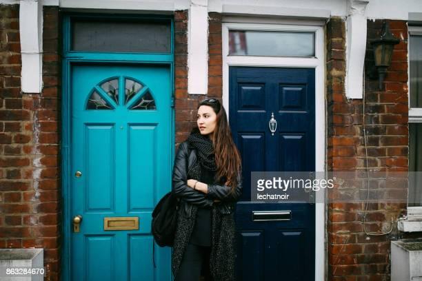 Joven esperando un taxi frente a su casa