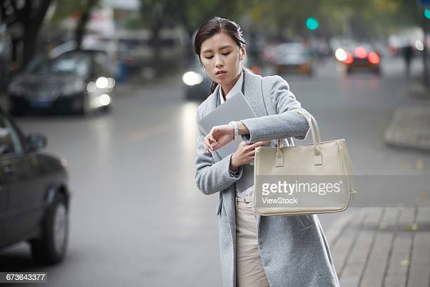 Young woman waiting for a taxi on the road