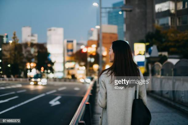 Young woman waiting for a taxi ride in downtown city street at dusk