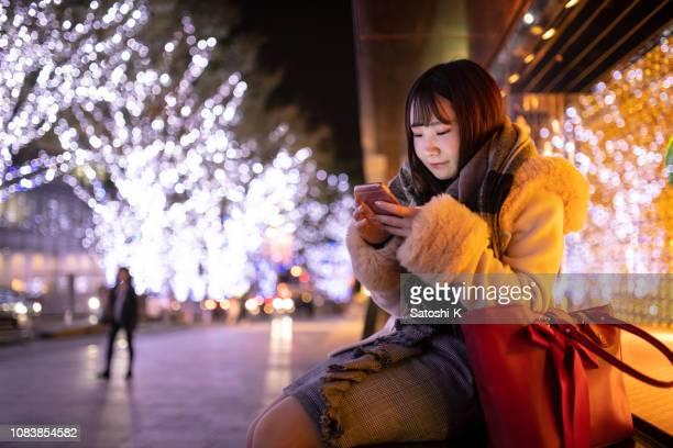 夜買い物に行く友人を待っている若い女性 - 待つ ストックフォトと画像